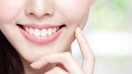 아름 다운 젊은 여자 건강 치아를 닫습니다 매력적인 미소. 녹색 배경에 고립, 아시아 아름다움