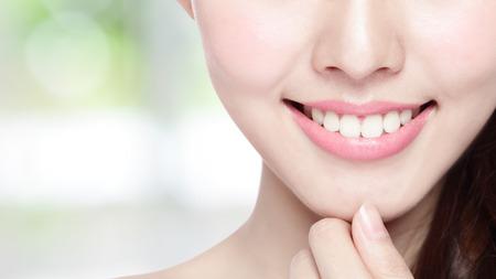 dentisterie: Belles jeunes dents de la santé de la femme se referment et charmant sourire. Isolé sur fond vert, la beauté asiatique