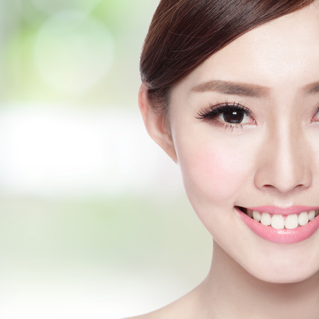 asia women: Half portrait of the woman with beauty face, perfect skin and health teeth, she smile to you isolated on nature green background, asian beauty