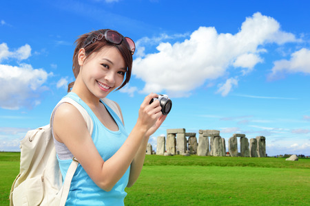 english girl: Happy woman traveler in Stonehenge, an ancient prehistoric stone monument , UK. in England,  asian girl Stock Photo