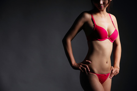 adult sex: Attractive Sexy woman with beautiful body posing and wear red underwear isolated on gray background, asian beauty