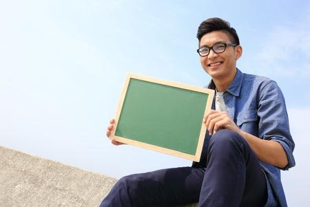 asian teacher: Happy man holding blackboard or chalkboard with sky background, asian male Stock Photo