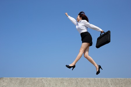 side profile: Successful business woman jump and run with blue sky background, full length, asian