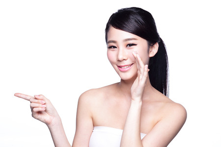 Beautiful young woman with healthy clean skin presenting something on her hand. Isolated on white. asian beauty