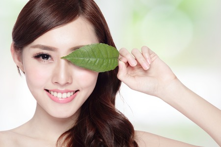 adult care: beautiful woman face portrait with green leaf , concept for skin care or organic cosmetics , asian beauty
