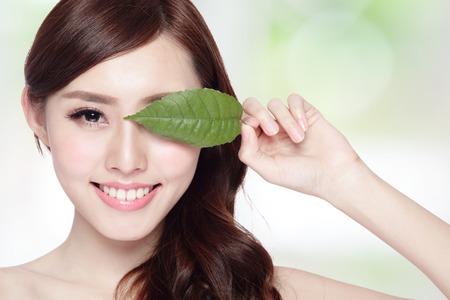 mooie vrouw gezicht portret met groen blad, concept voor huidverzorging of biologische cosmetica, Aziatische schoonheid