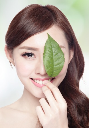 herbal cosmetics: beautiful woman face portrait with green leaf , concept for skin care or organic cosmetics , asian beauty