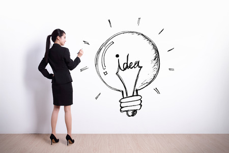idea concept - Back view of business woman writing idea and light bulb on white wall background