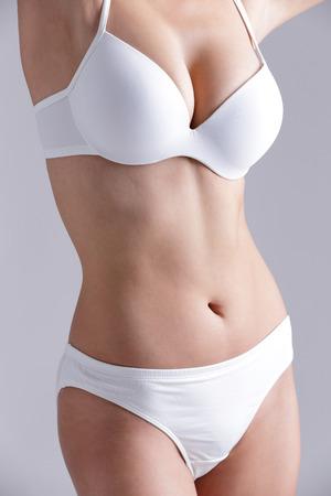 Mooie slanke lichaam van de vrouw die op grijs