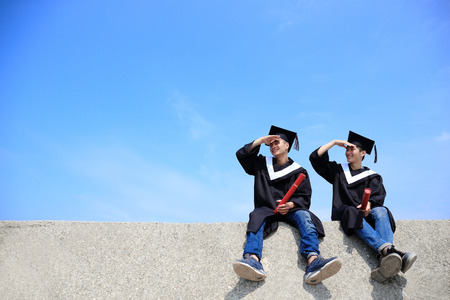 gown: Two happy graduates student look sky , asian