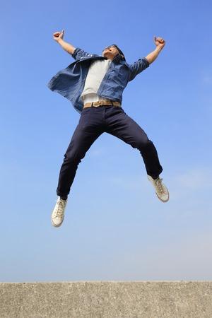 gente saltando: Hombre feliz del estudiante universitario correr y saltar con fondo de cielo azul, de cuerpo entero, asi�tico macho