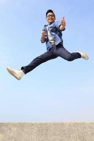 gente saltando: Hombre feliz del estudiante universitario correr y saltar con cielo azul, de cuerpo entero, asi�tico macho