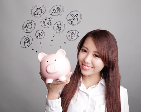 piggies: Saving money concept - woman smiling happy and holding pink piggy bank isolated on white background. Asian beauty