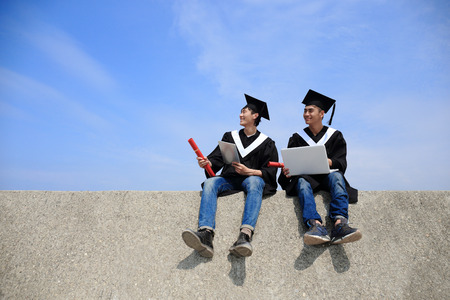 academic robe: Two happy graduates student use digital tablet pc and laptop computer with sky , asian Stock Photo