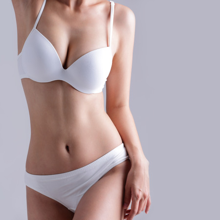 slim tummy: Beautiful slim body of woman isolated on gray