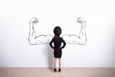 Back view of business woman with sketched strong and muscled arms, she look white wall