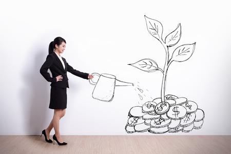 Groei concept - Zakenvrouw drenken een plant die geld boom produceert Stockfoto