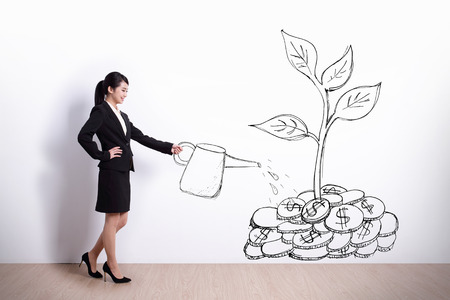 grow: Growth concept - Businesswoman watering a plant that produces money tree