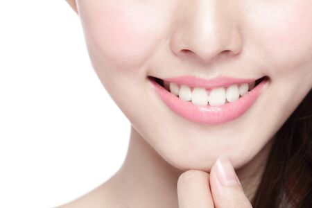hands in mouth: Beautiful young woman health teeth close up and charming smile. Isolated over white asian beauty