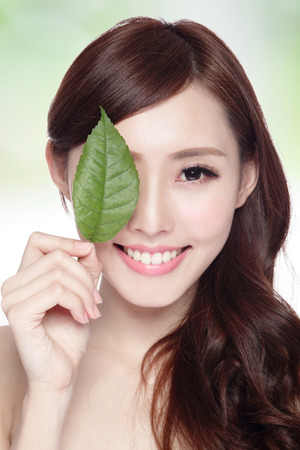 young leaves: beautiful woman face portrait with green leaf , concept for skin care or organic cosmetics , asian beauty