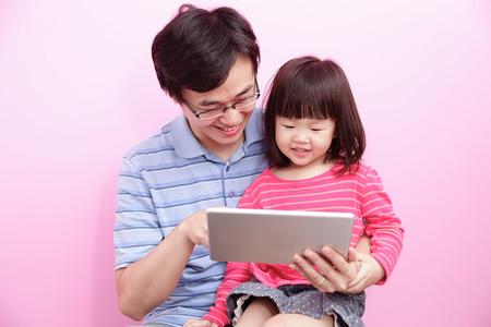 Gelukkige vader en dochter maken gebruik van digitale tablet pc die over een roze achtergrond, Aziatische familie