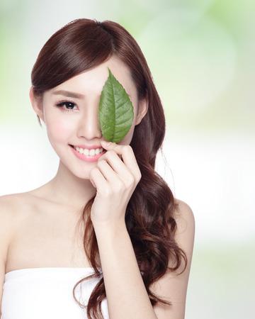 ojos verdes: hermoso retrato cara de la mujer con la hoja verde, concepto para el cuidado de la piel o los cosméticos orgánicos, belleza asiática