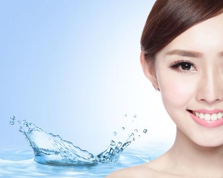 bellezza: Concetto di bellezza Cura della pelle, Bella donna faccia con schizzi d'acqua isolato su sfondo blu, modello asiatico