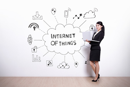 business woman hold computer with drawing internet of things icon and text on white wall background, asian Stock Photo