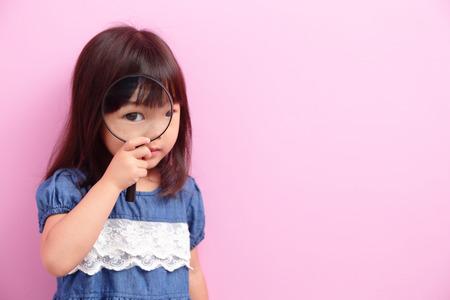 Glückliches Kind Mädchen lächeln und denken, dass etwas isoliert auf rosa Hintergrund, asiatisch