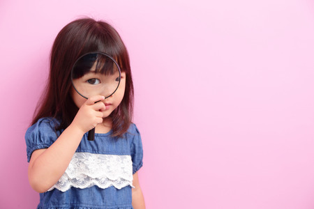 dream vision: Happy kid girl smile and think something isolated on pink background, asian