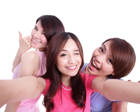 group picture: Selfie - Happy teenagers woman taking pictures by themselves isolated on white background, asian Stock Photo