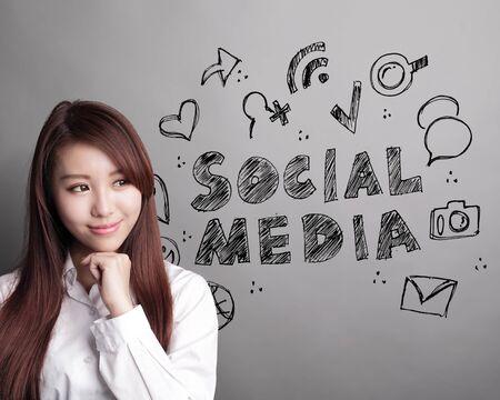 trabajo social: Social Media concepto - mujer de negocios que mira el texto Los medios sociales y el icono sobre fondo gris, asi�tico