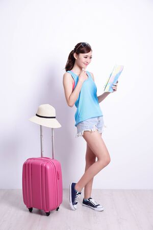 baggage: Happy woman tourist travel look map and think something with white concrete wall and wood floor, asian beauty