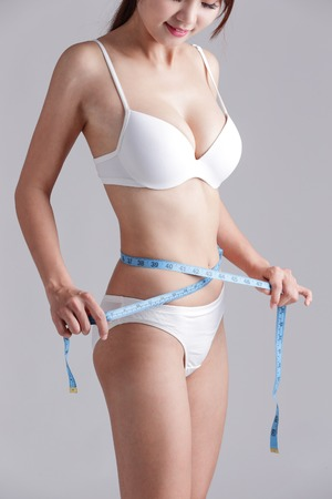 forme: Femme mesurant forme de belle taille pour concept de modes de vie sains avec un fond gris, la beauté asiatique