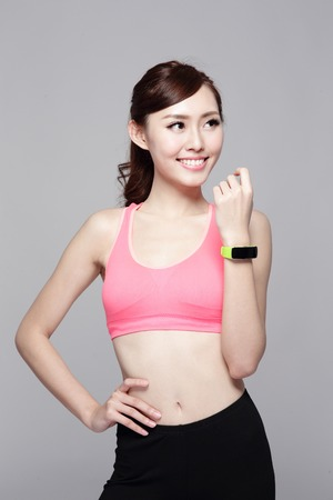 beauty and health: Health sport woman wearing smart watch device with touchscreen doing exercises isolated on gray background, asian beauty Stock Photo