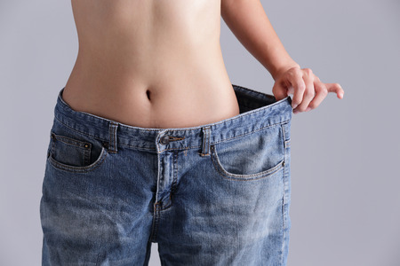 women hips: woman shows weight loss by wearing old jeans, asian beauty