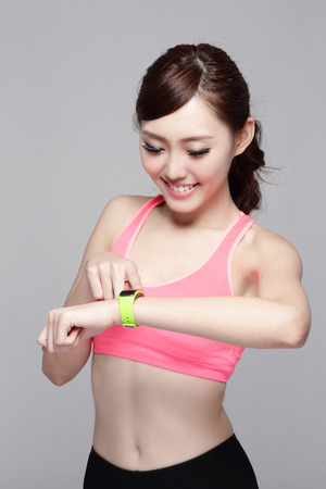 Health sport woman wearing smart watch device with touchscreen doing exercises isolated on gray background, asian beauty photo