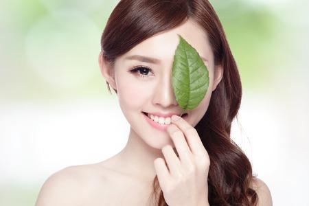 красота: красивая женщина лицо портрет с зеленым листом, концепция для ухода за кожей или органической косметики, азиатской красоты