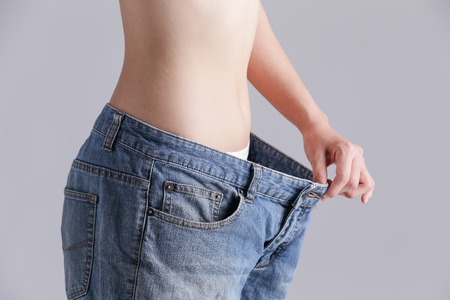 underwear girl: woman shows weight loss by wearing old jeans, asian beauty