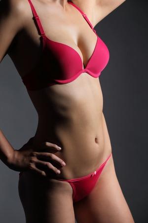 hot breast: Привлекательная секси женщина с красивой постановкой тела и носить нижнее белье, изолированных красной на сером фоне, азиатской красоты