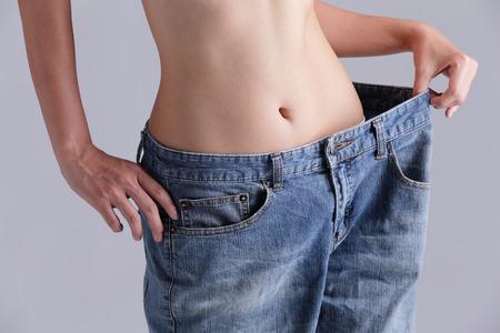 Žena ukazuje úbytek na váze tím, že nosí staré džíny, asijských krása