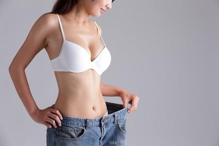 cintura: mujer muestra la pérdida de peso con el uso de pantalones vaqueros viejos, belleza asiática