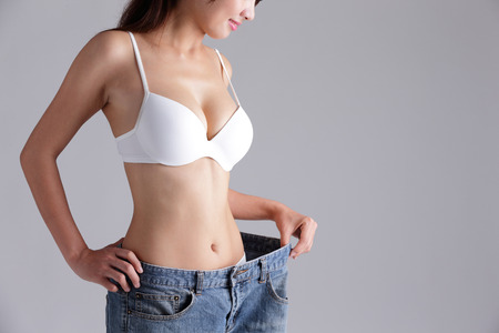 slim tummy: woman shows weight loss by wearing old jeans, asian beauty