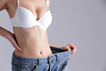 stomach: woman shows weight loss by wearing old jeans, asian beauty