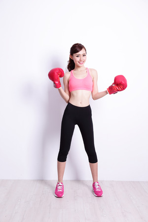 beauty and health: Fit woman boxing with health, attractive and slender figure, with white wall great for your design or text, asian beauty