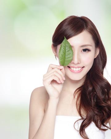 schoonheid: mooie vrouw gezicht portret met groen blad, concept voor huidverzorging of biologische cosmetica, Aziatische schoonheid