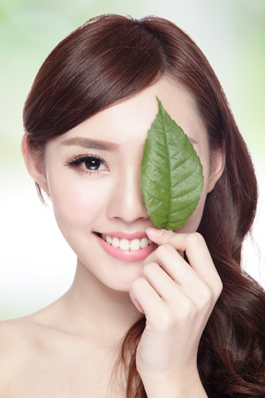 care for: beautiful woman face portrait with green leaf , concept for skin care or organic cosmetics , asian beauty