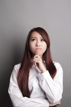 asian girl face: Thinking business woman and look copy space isolated on grey background with finger at face, asian beauty Stock Photo