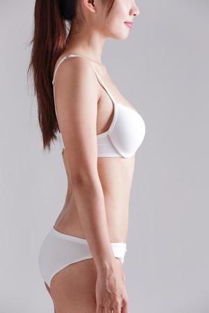 white panties: Profile of beautiful slim woman body isolated on gray background Stock Photo