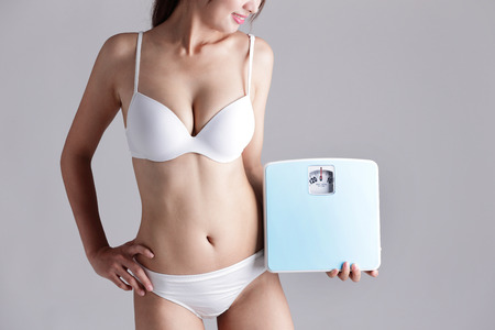 grey scale: Health and slim body of woman holding scale isolated on gray background, asian beauty